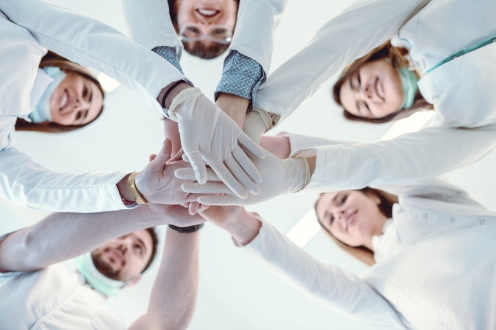 Dental team stacking hands for success.